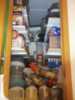 Attic access converted to a pantry with shelving loaded.