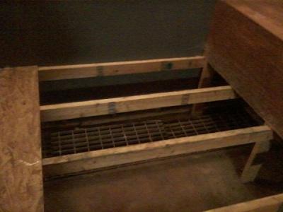 Garage style floor grate hidden under the built-in bed.